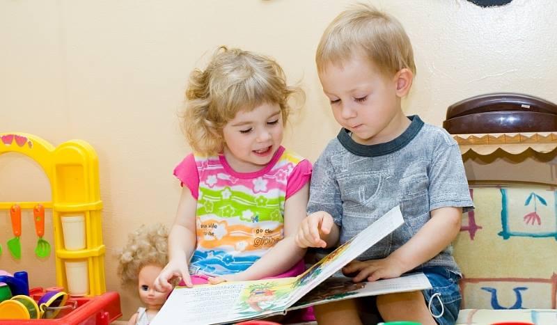 Девочка и мальчик листают книгу