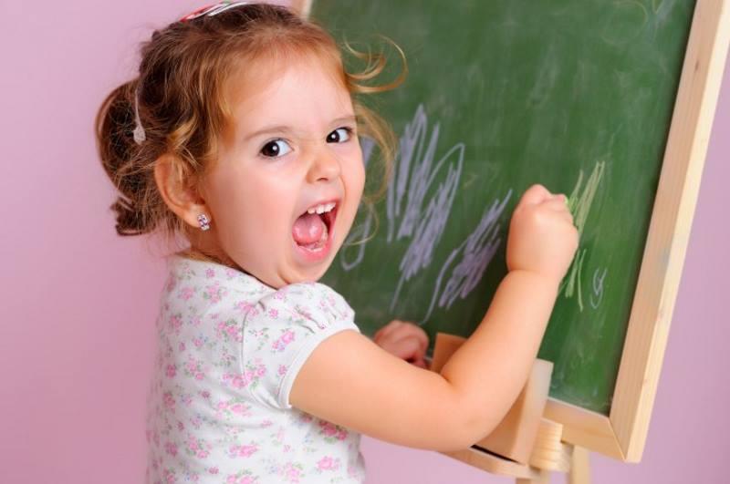 Девочка рисует на доске и кричит