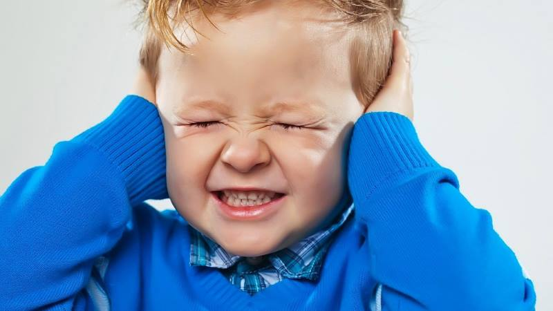 Ребенок закрывает уши руками