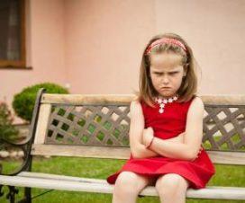 Обиженная девочка сидит на лавке