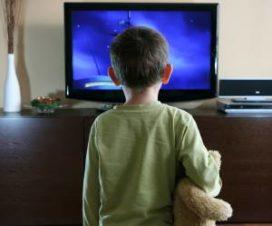 Ребенок с игрушкой перед телевзором